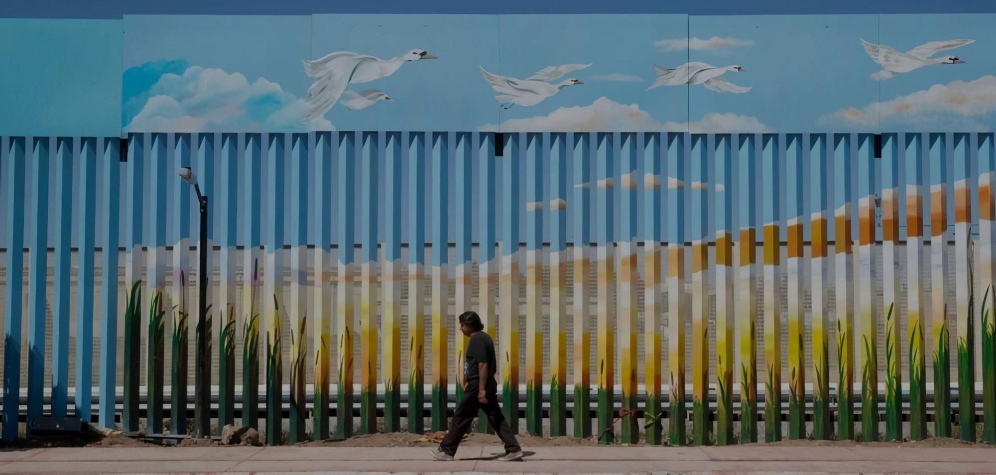A man walks past the painted border fence in Agua Prieta, Mexico. Residents of Agua Prieta and Douglas say they feel there's a good relationship between the two cities.